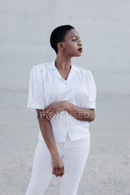 Élégante femme ethnique aux cheveux courts en chemise et pantalon blancs posant contre un mur gris — Photo de stock