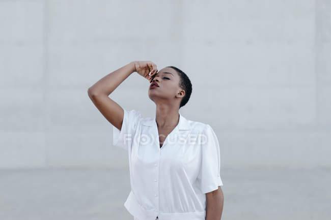 Mode kurzhaarige ethnische Frau in weißem Hemd posiert gegen graue Wand — Stockfoto