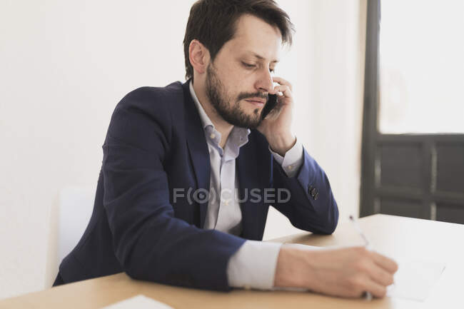 Concentrated young male talking on mobile phone and holding pen near papers at table in office — Stock Photo