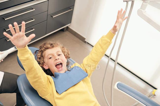 Glücklicher Junge liegt in Zahnklinik mit Blick auf Kamera mit ausgestreckten Armen — Stockfoto