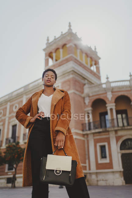 Confident African American elegant woman in costume holding bag on street — Stock Photo