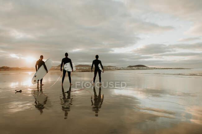 People with surfboard walking near sea — стоковое фото
