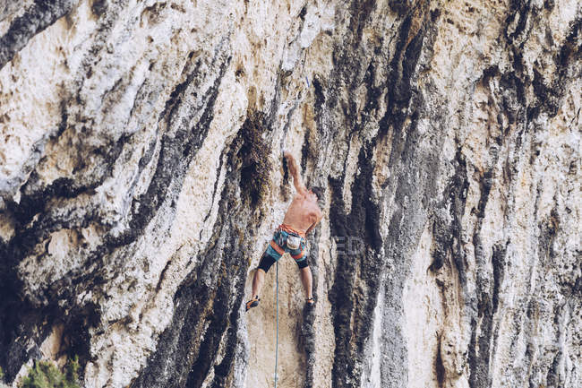Side view of unrecognizable male in shorts climbing up rough cliff on sunny day in countryside — Stock Photo