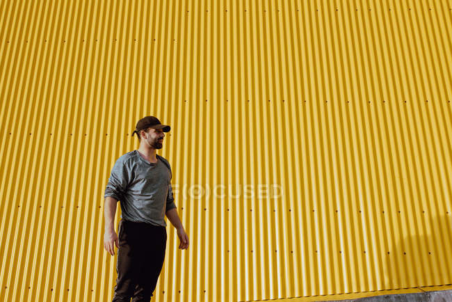 Bearded guy in trendy outfit standing against yellow wall of modern building on sunny day on city street — Stock Photo