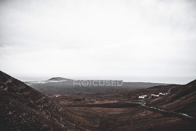 Picturesque view of valley with road and barren lands under stormy sky in Lanzarote, Canary Islands, Spain — Stock Photo