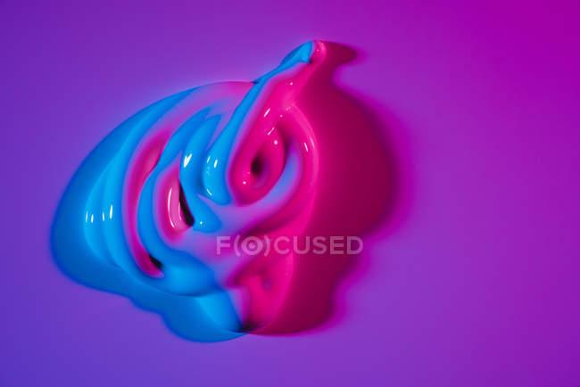 Калюж яскравого неонової акрилової фарби поширюються на яскраво-фіолетовий фон — стокове фото