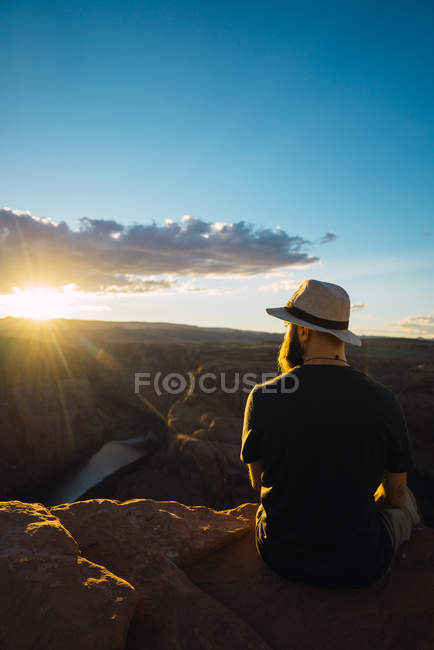 Back view of bearded guy with backpack looking at beautiful canyon and calm river on sunny day on West Coast of USA — Stock Photo