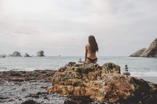 Vista posteriore di nuda signora bruna in lingerie seduta sulla roccia sulla costa del mare — Foto stock