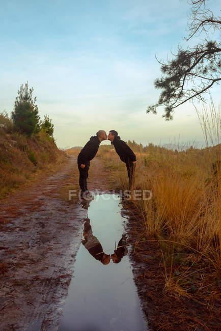 Водоотвод с общением гомосексуальной пары и поцелуями на дороге — стоковое фото