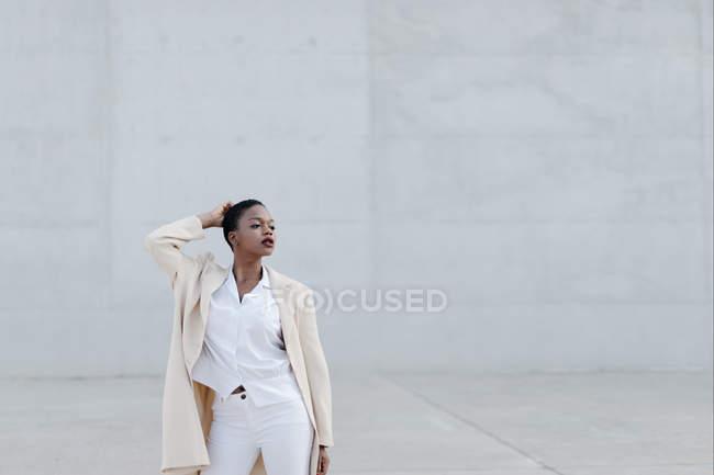 Femme à poil court de la mode posant contre le mur gris — Photo de stock