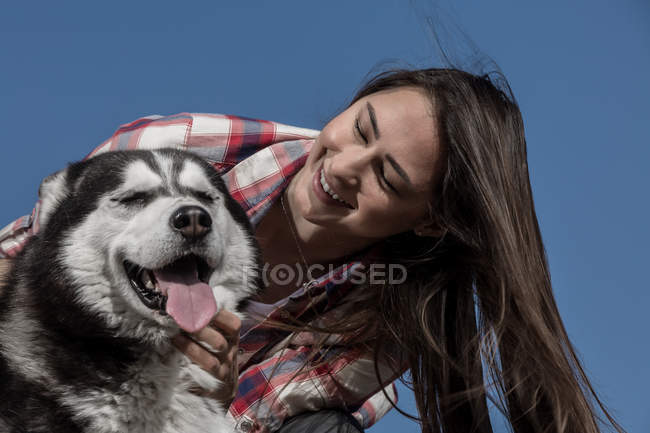 Smiling young woman hugging husky in front of blue sky — Stock Photo
