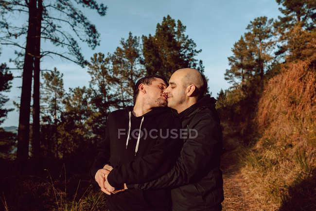 Гомосексуальная пара обнимается и целуется на дорожке в лесу в солнечный день на размытом фоне — стоковое фото
