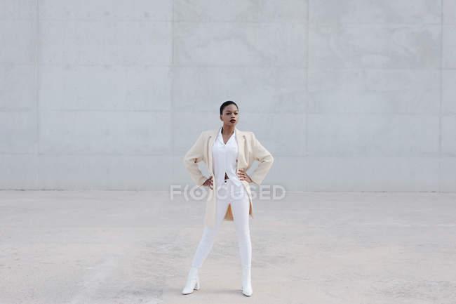 Mode kurzhaariges Model in weißem Outfit posiert gegen graue Wand — Stockfoto