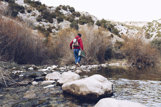 Back view of casual woman carrying case and jumping on rocks of clear stream of water in nature — Stock Photo