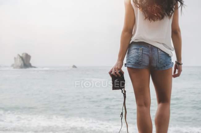 Вид сзади женщины с камерой, стоящей на пляже и смотрящей на вид на море — стоковое фото