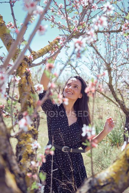 Молода усміхнена жінка в одязі стояв за квітучими плодовими деревами — стокове фото