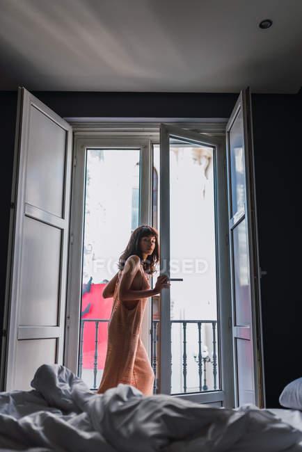 Giovane donna magra in abito nudo in piedi vicino al balcone in camera da letto — Foto stock