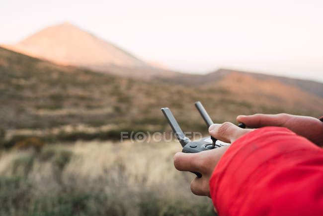 Closeup of human hands holding joystick with barren landscape on background — Stock Photo