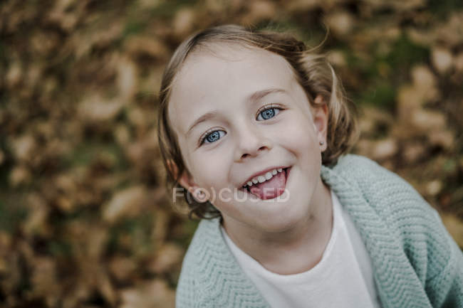 Positive child with tongue out looking at camera in park with dry foliage on blurred background — Stock Photo