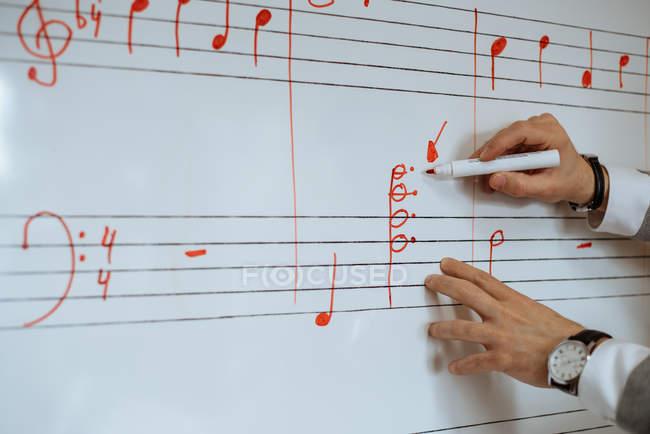Неузнаваемый человек пишет ноты на белой доске в консерватории. — стоковое фото