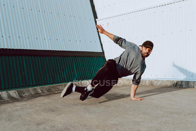 Guy performing handstand while dancing near wall of modern building — Stock Photo
