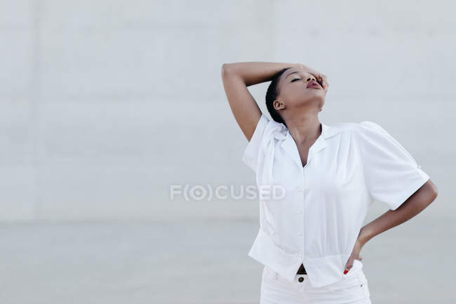 Fashion short haired ethnic woman in white shirt posing against grey wall — Stock Photo