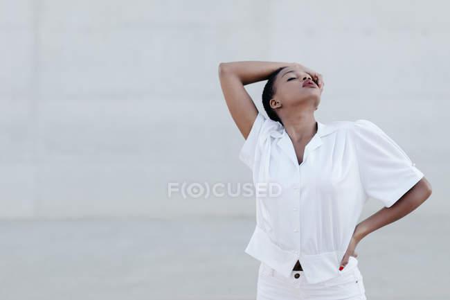 Мода короткий волосся етнічної жінки в білій сорочці постановки проти сірої стіни — стокове фото