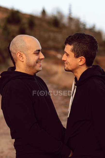 Vista laterale della coppia omosessuale che si abbraccia e si guarda lungo il sentiero nella foresta nella giornata di sole — Foto stock