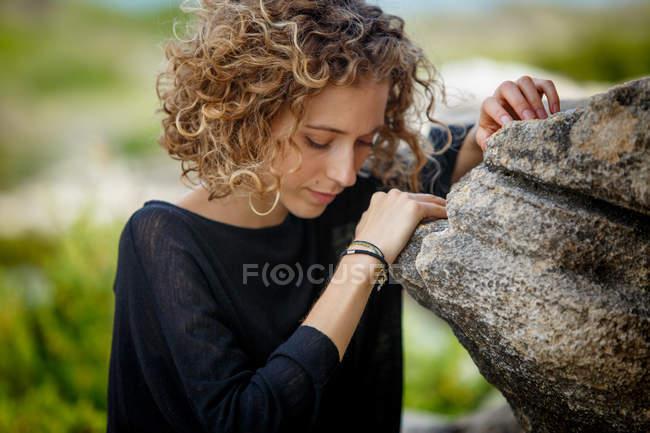 Giovane donna premurosa appoggiata sulla roccia in natura su sfondo sfocato — Foto stock