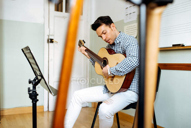 Schöner Mann spielt Gitarre während der Probe im Tonstudio. — Stockfoto