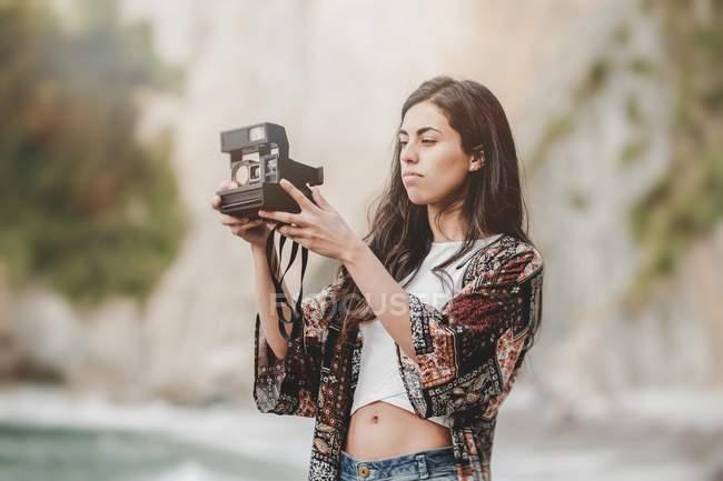 Молода жінка перевірка камери на морському узбережжі — стокове фото