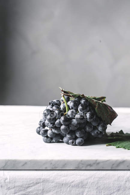 Bunch of grapes with leaves on table — Stock Photo
