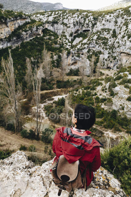 Back view of traveling woman with backpack sitting on high rocky cliff observing beautiful valley — Stock Photo