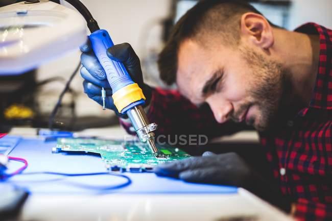 Primo piano dell'uomo che ripara la scheda madre con saldatura sul posto di lavoro — Foto stock