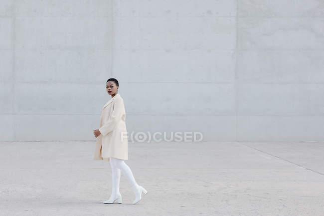 Mode femme ethnique aux cheveux courts en tenue blanche marchant devant un mur gris — Photo de stock