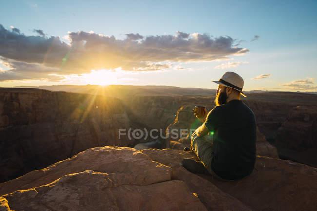 Vue latérale du gars barbu dans le chapeau profitant de boissons chaudes et regardant coucher le soleil tout en étant assis près du merveilleux canyon sur la côte ouest des États-Unis — Photo de stock