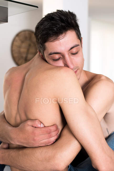 Passionate sexual shirtless gay couple hugging in an intimate moment in the kitchen countertop — Stock Photo
