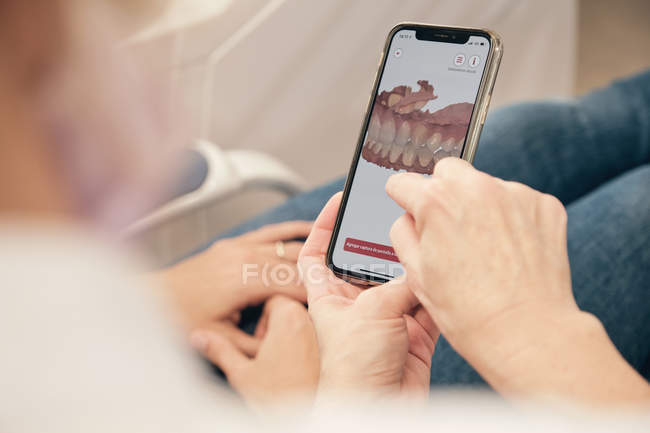 Anonymous dentist demonstrating smartphone with teeth scan to unrecognizable patient in clinic — Stock Photo