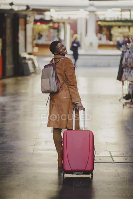 Femme élégante afro-américaine souriante avec des bagages marchant dans la rue près de petits magasins — Photo de stock