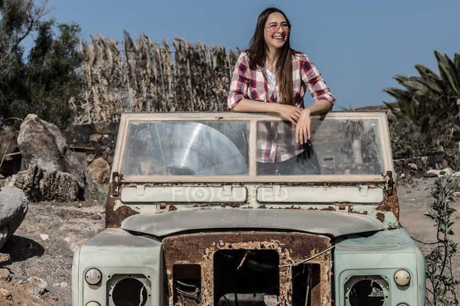Allegra giovane donna in occhiali da sole in piedi in auto deserta in natura — Foto stock