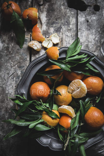 Fresh mandarins with leaves and platter on grey wooden table — Stock Photo