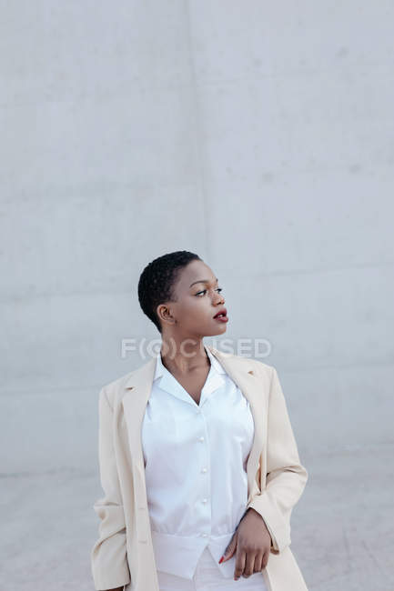 Elegant fashion short haired ethnic woman posing against grey wall — Stock Photo