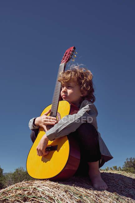Garçon mignon étreignant guitare acoustique et chantant tout en étant assis dans un énorme rouleau de foin sec par une journée ensoleillée à la campagne — Photo de stock