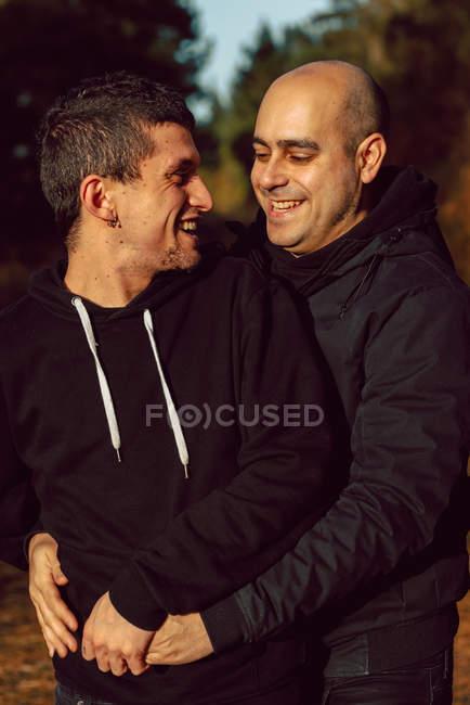 Веселая гомосексуальная пара, обнимающаяся в лесу в солнечный день на размытом фоне — стоковое фото