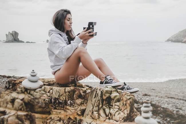 Жінка в пуловер і взуття з ретро-камерою сидячи на скелястому узбережжі — стокове фото