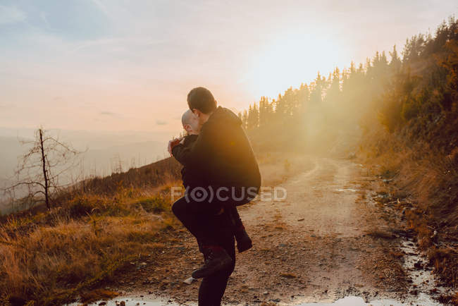Happy homosexual couple having fun on route between plants on mountain and blue sky — Stock Photo