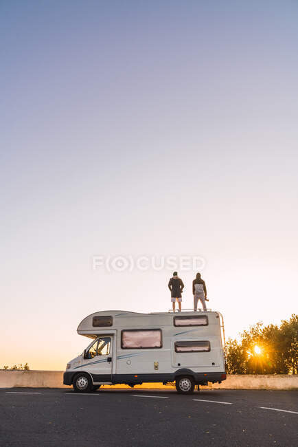 Вид сзади парней на крыше передвижного дома по асфальтированному маршруту и живописное голубое небо вечером в Тенерифе, Канарские острова, Испания — стоковое фото