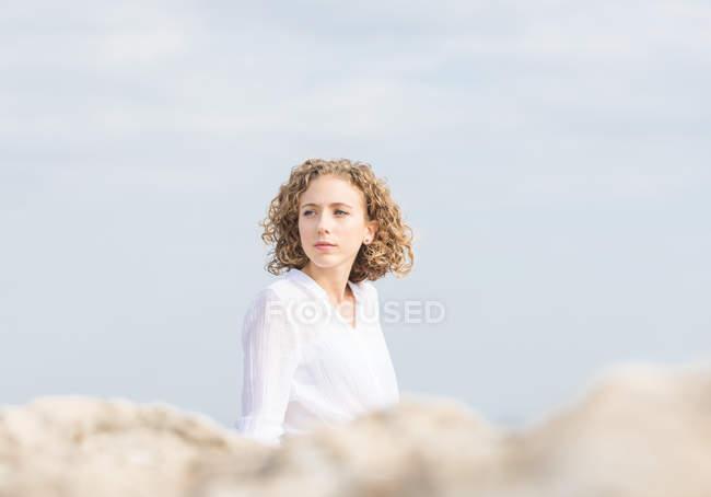 Junge nachdenkliche Frau sitzt an der Küste und schaut weg — Stockfoto