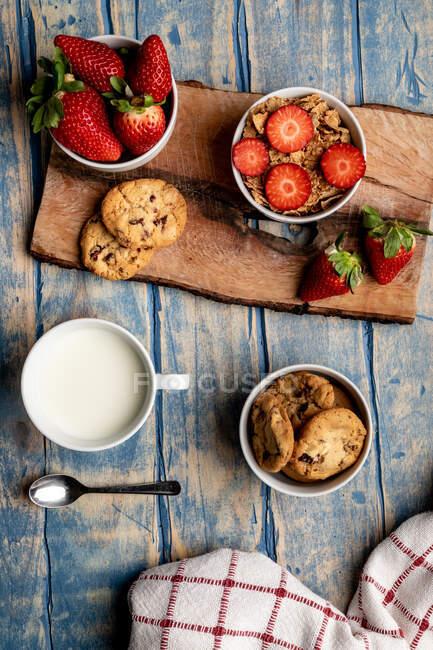 Vidro e garrafa de leite e pilha de biscoitos frescos em tábua de madeira perto guardanapo — Fotografia de Stock