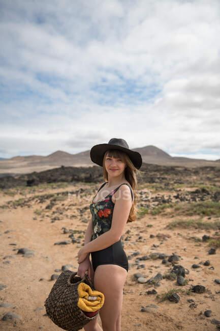 Vista lateral de la encantadora joven en elegante traje de baño y sombrero bolsa de mano con toallas y mirando a la cámara mientras está de pie en el increíble campo en el día nublado y sonriendo - foto de stock
